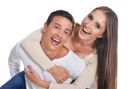 Ritratto di giovane coppia felice che si abbraccia su sfondo bianco