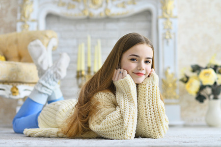 Mooi tienermeisje dat op de vloer in de kamer ligt Stockfoto