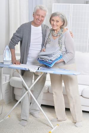Portrait of happy senior couple during ironing