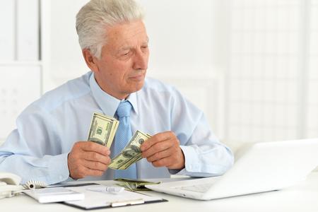 Portret van zelfverzekerde senior zakenman die geld aanhoudt Stockfoto