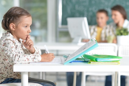 Portrait of cute little girl sitting in classroom Imagens