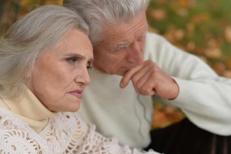 Close up portrait of sad senior couple in autumn park Imagens