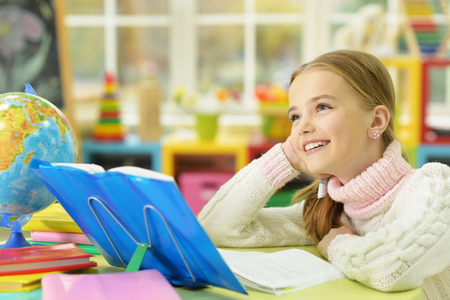 Cute girl leaning on hand while doing her homework