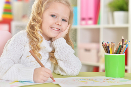 Portrait of happy girl drawing with colorful pencils Standard-Bild