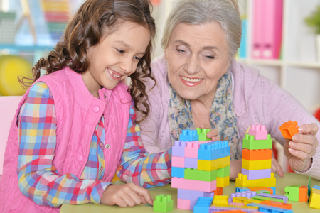 Close up portrait of cute girl and grandmother playing