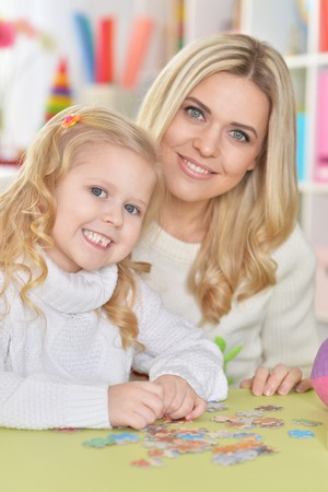 Portrait of mother with little daughter collecting puzzle