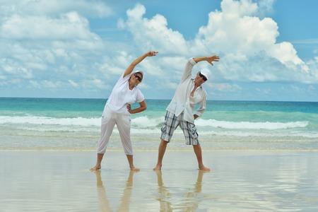 Portrait of elderly couple on tropical beach exercising