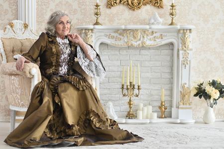 Portrait of beautiful senior woman in dress Queen, posing indoors