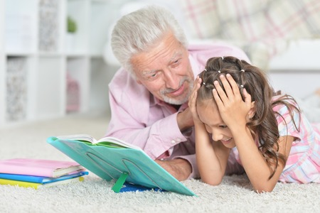 Close-up portrait of grandfather reading book with his little granddaughter