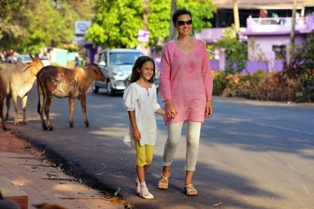 Portrait of mother and daughter walking on road