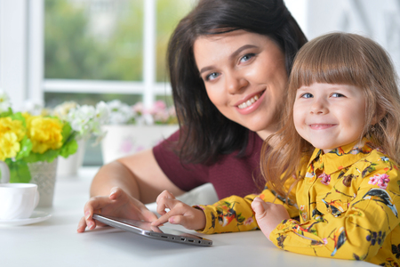 Mother and daughter playing game on laptop Imagens - 121944227