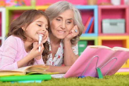 Cute schoolgirl doing homework with her grandmother