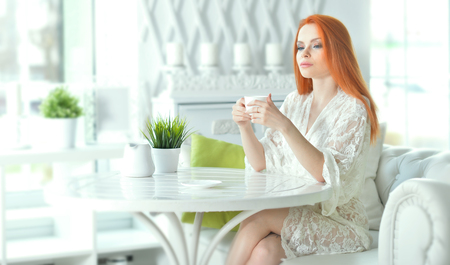 Portrait of beautiful redhead young woman drinking tea