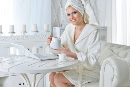 Young woman after shower sitting in front of laptop Stock Photo