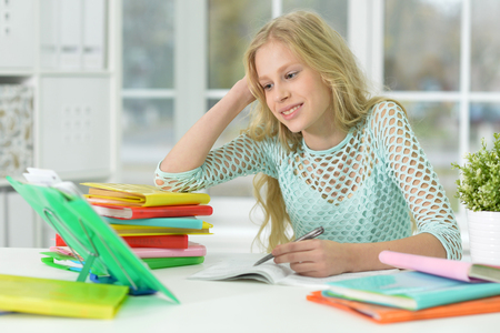 Schoolgirl sitting at desk and studying at home