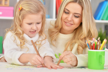 Portrait of mother with little daughter drawing together