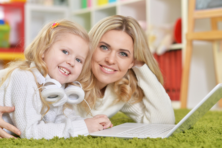 Portrait of mother with little daughter using laptop while lying on floor Imagens
