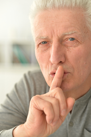 Close up portrait of senior man with finger on lips 写真素材 - 122165453