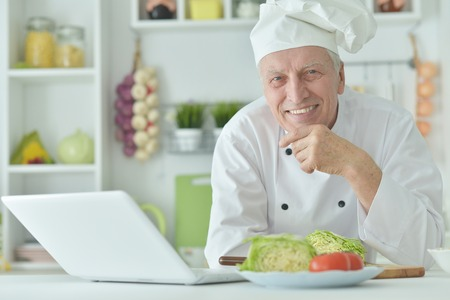 Portrait of elderly male chef cooking at table with laptop 写真素材
