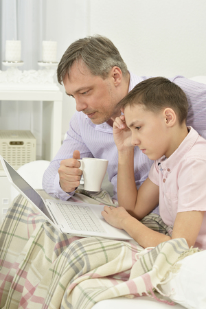 Portrait of father and son with laptop