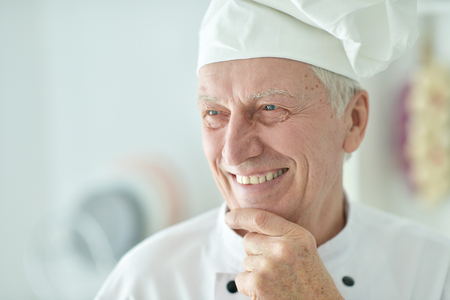 Close-up portrait of happy elderly male chef posing at home