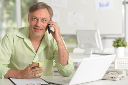 Portrait of businessman talking on phone while working with laptop