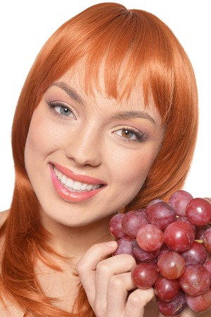 Beautiful redhead young woman with red grapes posing isolated on white background Banque d'images - 122537965