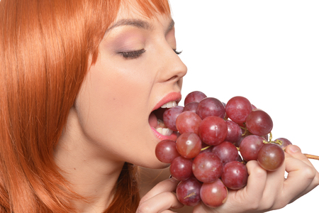 Beautiful redhead young woman with red grapes posing isolated on white background