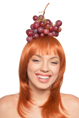 Beautiful redhead young woman with red grapes on head isolated on white background