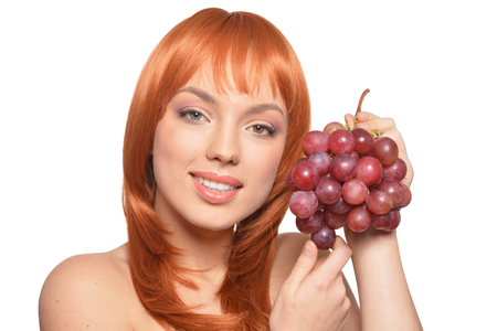 Beautiful redhead young woman with red grapes posing isolated on white background Banque d'images - 122537982