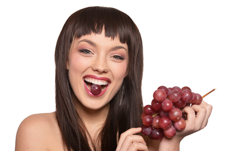 Young woman posing with grapes isolated on white background Banque d'images - 122538665