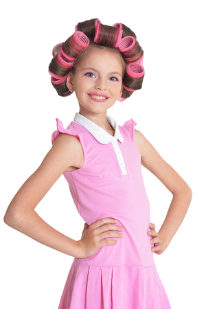 Portrait of emotional little pretty girl with hair curlers posing isolated