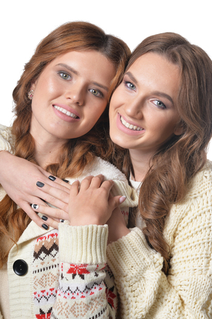 Two beautiful young women posing, close up portrait on white background