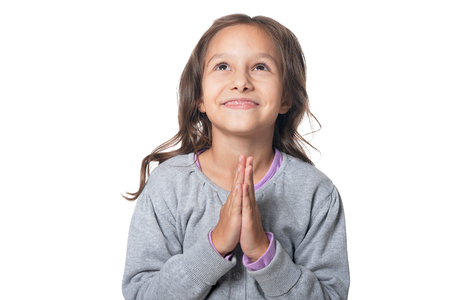 Portrait of cute little girl posing and praying against white