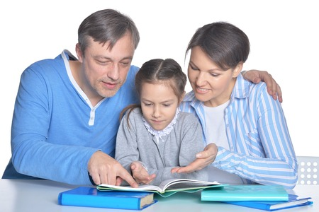 Parents with daughter reading books on white background