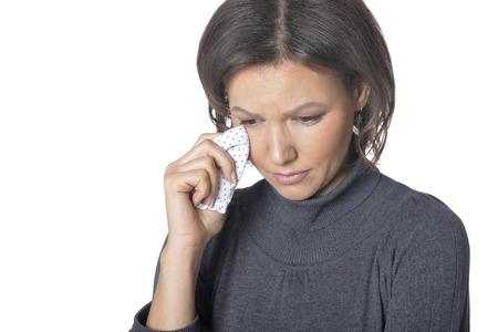 Studio portrait of beautiful brunette woman crying isolated