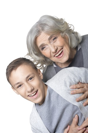 Portrait of grandmother and grandson having fun on white background