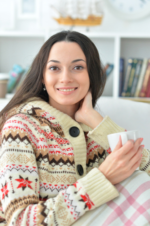 Portrait of young beautiful woman with a cup of tea on sofa at home 版權商用圖片