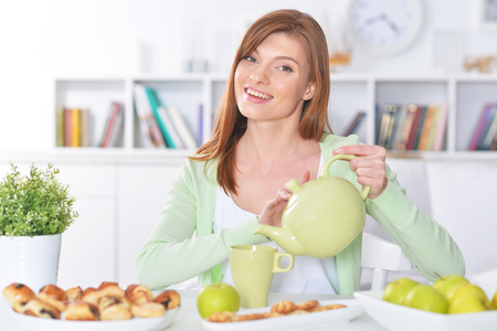 Beautiful young woman pouring tea in cup Reklamní fotografie