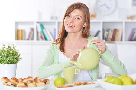 Hermosa joven vertiendo té en taza Foto de archivo