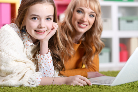 Young woman with girl using laptop at home 版權商用圖片