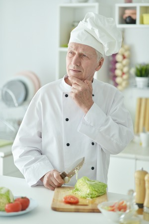 Portrait of elderly male chef cooking at kitchen