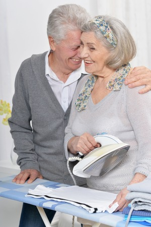 Close-up portrait of happy senior couple during ironing