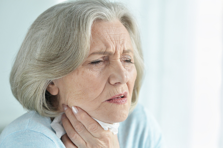 Close-up portrait of ill senior woman posing at home Stock Photo