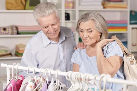 Portrait of happy senior couple near rack with shirts