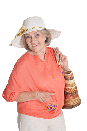 Beautiful senior woman in white hat on white background. Travel concept