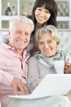 Close-up portrait of happy family with laptop at home