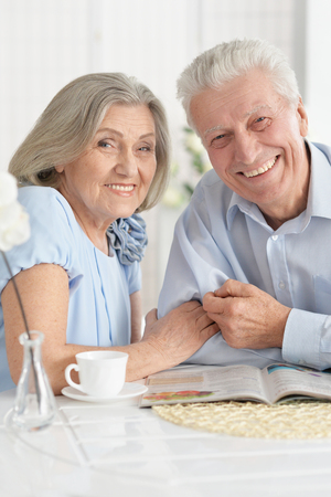 Portrait of mature couple with magazine drinking tea Imagens
