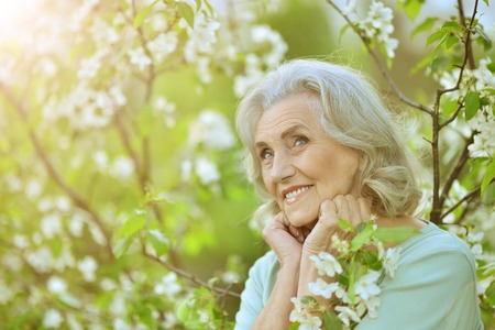 Beautiful senior woman posing near blooming tree