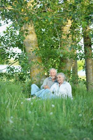 Nice mature couple sitting on green grass